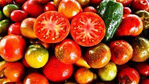 ein Haufen verschiedener Tomaten und ganz oben zwei Tomatenhälften