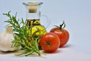 ein kleines Fläschchen Olivenöl, davor eine Knoblauchzehe, ein kleiner Rosmarizweig und daneben zwei kleine Tomaten