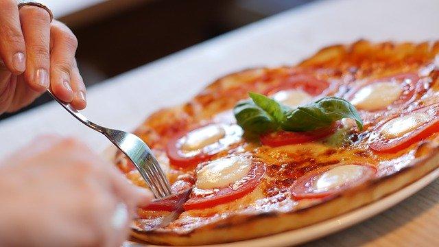 eine Person in einem Restaurant die beginnt ihre Caprese Pizza zu essen