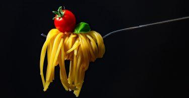 eine Gabel mit aufgerollten Spaghetti einer Kirschtomate darauf und ein Basilikumblatt, schwarzer Hintergrund