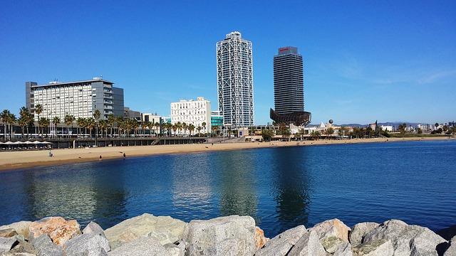 Aussicht von den Felsen auf den leeren Strand Barcelonas mit tiefblauem Meer