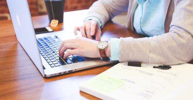 eine Frau mit hellblauer bluse und graue Strickjacke die an einem Holztisch sitzt und an einem laptop schreibt, rechts von ihr eine Tasse Tee und links ein offenes buch