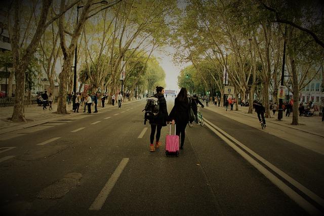 zwei junge Frauen die mit ihren Koffern die Straße der Rambla runterlaufen