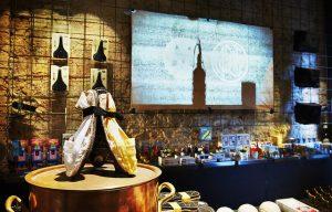 ein Laden mit verschiedenen Produkten umgeben von Steinmauern und einer Projektion