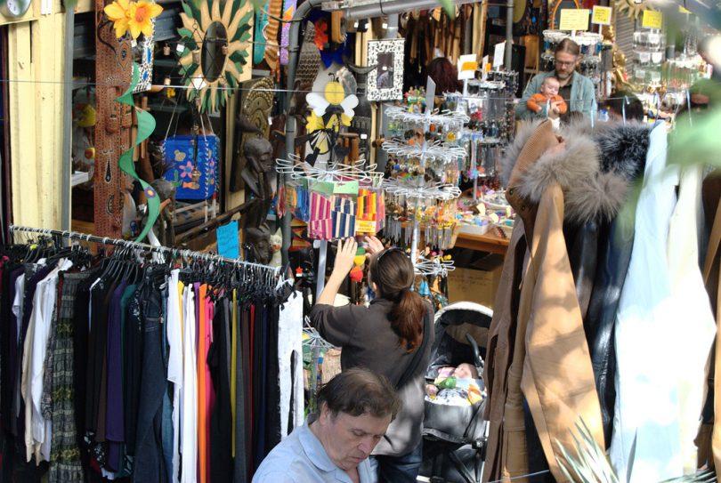Strassenflohmarkt mit Personen die durch die Kleiderständer stöbern