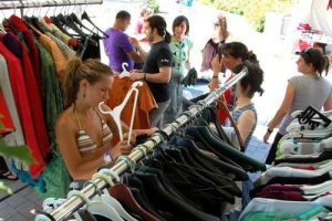 mehrere Leute die durch die Kleiderständer eines Verkaufstands schauen