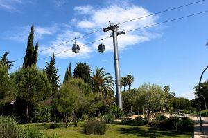 ein Ausschnitt der Seilbahn die zum Montjuïc hochfährt, darunter Wiese, Palmen und Bäume
