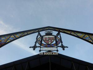 das Wappenzeichen des Boqueria Marktes von unten gesehen mit den Buchstaben La Boqueria und dem bunten Kristalbogen darüber