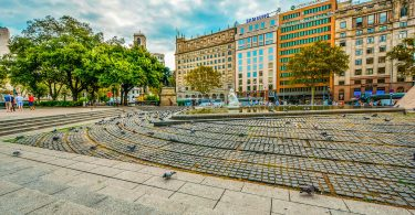 ein großer Platz in Barcelona mit Bäumen einem Springbrunnen und kreisförmig angelegte Pflastersteine