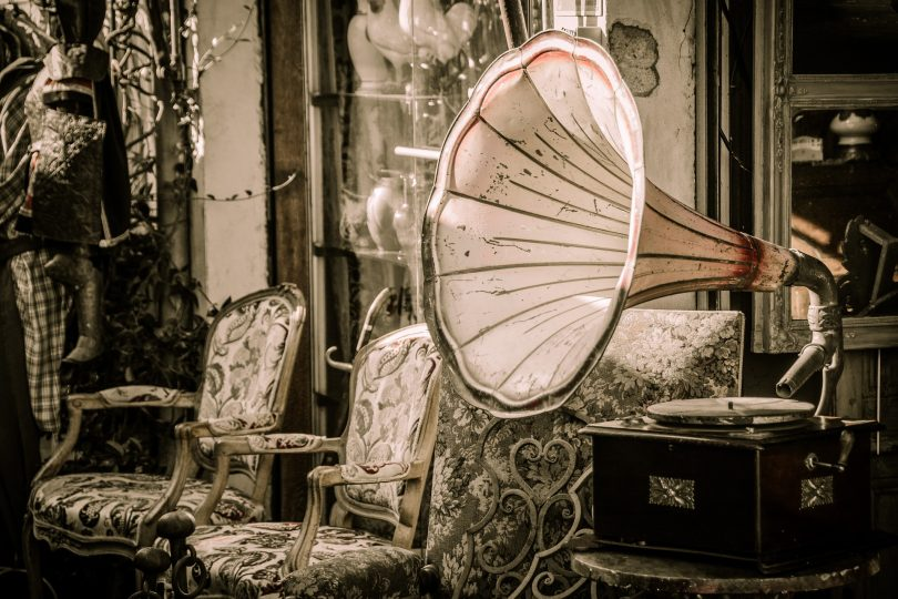 eine Ecke eines Antiquitätenladens auf dem ein alter Plattenspieler und zwei vintage Sessel zu sehen sind