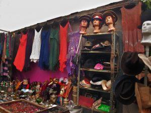 Flohmarktstand mit bunten Kleidern und Hüten aller Art