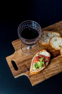 Holzbrett auf dem ein kleines Glas mit Rotwein steht und eine Weissbrotscheibe mit Tomate und Avocado