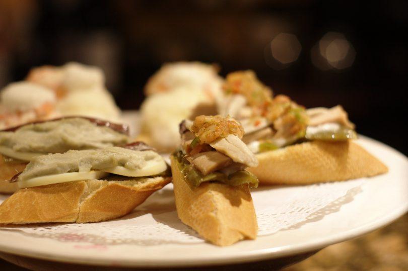 Weisser runder Teller mit Pintxos: je eine Scheibe Baquette mit grüner Paprika und Sardelle