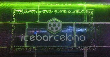 Ein Schild aus Eis, grün beleuchtet auf dem dem icebarcelona steht, bei nacht