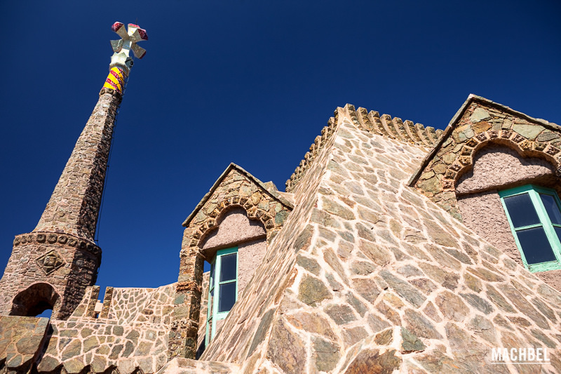 der obere Teil des Gebäudes aus braunen steinen mit türquis gestrichenen Fensterrahmen