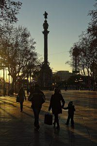 im Hintergrund die Kolumbusstatue bei Sonnenuntergang und im Vordergrund eine Familie mit einem kleinen Kind, alle warm eingepackt und die Frau hält eine Einkaufstüte in der linken Hand