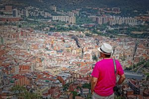 Ein Mann mit einem weisen Hut und einer kleinen Tasche umhängen, er trägt ein Pinkes T-Shirt und steht auf einem Aussichtspunkt und schaut auf die Stadt herab
