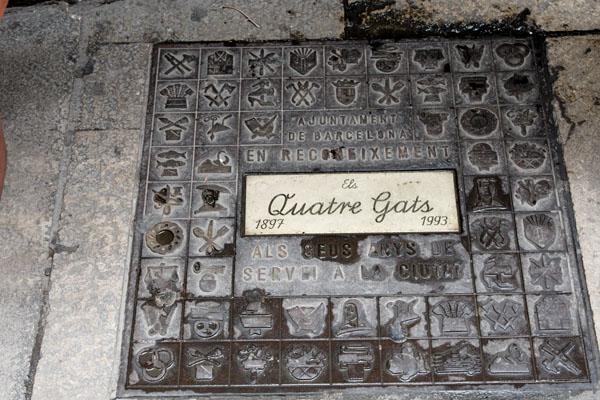 eine metallplatte auf dem Boden die mit verschiedenen Zeichen dekoriert ists und in der Mitte steht in Schreibschrift Qutatre Gats