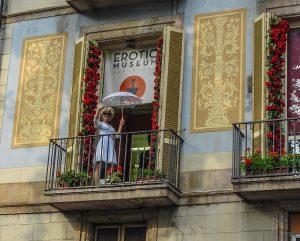 auf dem Balkon des Erotik Museums steht Marilyn Monroe in einem blauen Kleid mit einem weißen Sonnenschirm und winkt den Passanten zu