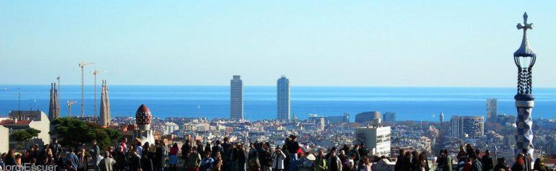 ein Aussichtspunkt mit vielen Menschen die auf Barcelona und das tief blaue Meer schauen