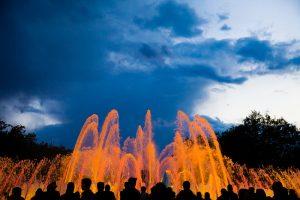 Orangenes Lichtspiel der Fontänen bei Dämmerung mit den Schatten der Zuschauer davor
