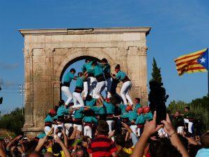 der Aufbau einer Menschpyramide der Catellers mit weissen Hosen und Türkisen T-Shirts, drum herum viele Leute die sie anfeuern und rechts im Bild eine katalanische Unabhängigkeitsflagge