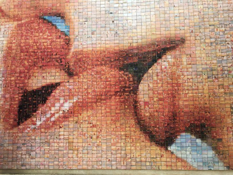 ein Wandmosaik auf dem zwei küssende Münder zu sehen sind