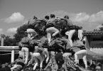 ein schwarz-weiss Foto von einer Bastlers Gruppe die gerade eine Menschenpyramide bilden