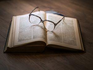 ein offenes Buch auf einem Holztisch mit einer Brille darauf