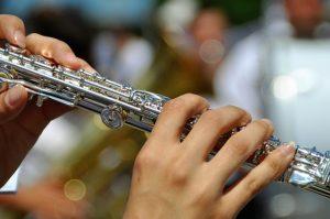 zwei Hände mit langen Fingernägeln die grade auf einer Querflöte spielen