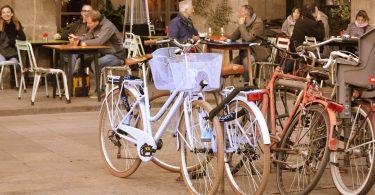 mehrere Fahrräder die vor einer Terrasse eines Café geparkt sind