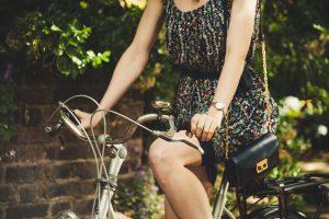 eine Frau im Kleid mit einer kleinen Tasche umhängen die gerade mit dem Fahrrad durch die Strassen fährt