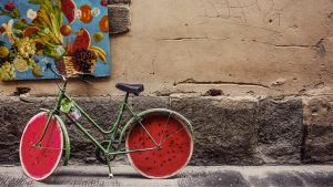 ein grünes Fahrrad mit reifen die aussehen wie Wassermelonen das vor einer Steinwand mit einem Obstgemälde steht
