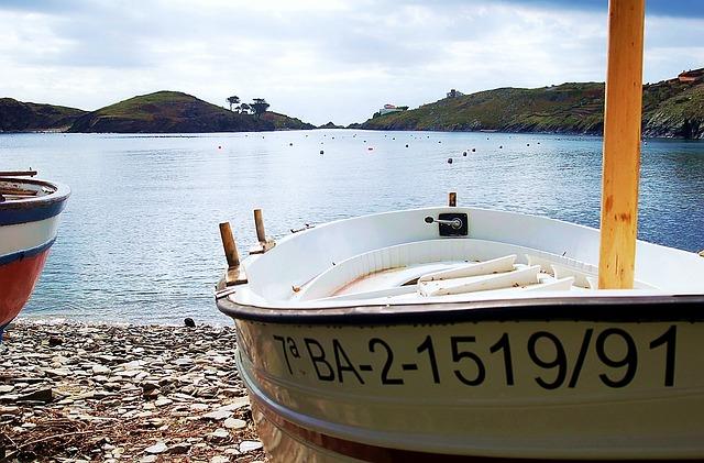 ein Fischerboot am Strand einer Bucht die fast komplett von Bergen umzingelt ist, auf dem beigen Boot steht 7aBA-2-1519/91