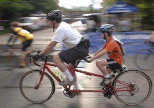ein mann und ein junge beide mit Helm die auf einem rotem Tandem auf der Strasse fahren