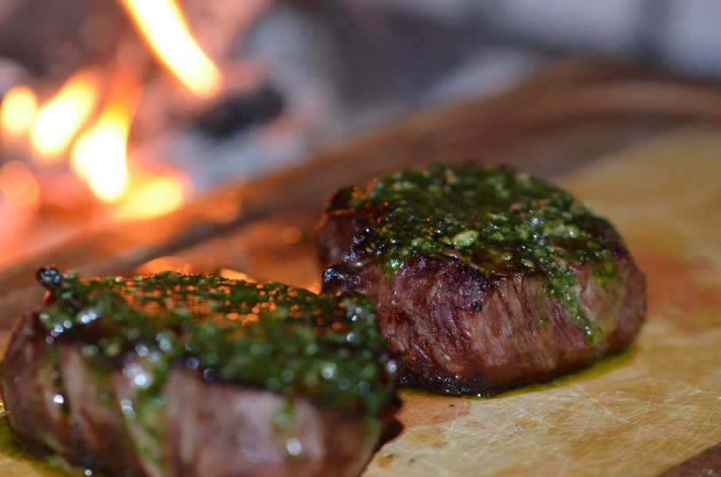 zwei saftig angebratene Steaks mit grünem chimichurri darauf