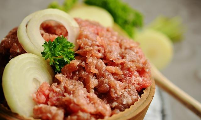 ein kleines Schüßelchen gefüllt mit Steaktartar, etwas Petersilie und zwei Zwiebelringen
