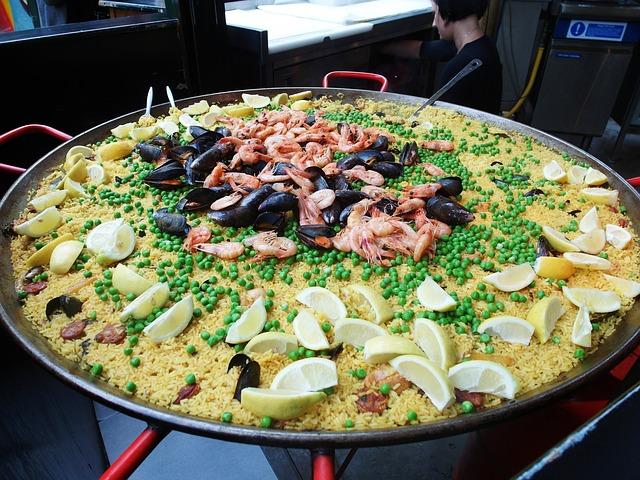 Eine große Paella in der traditionellen Pfanne mit vielen Zitronenstücken drumherum und in der Mitte Garnelen und Miesmuscheln