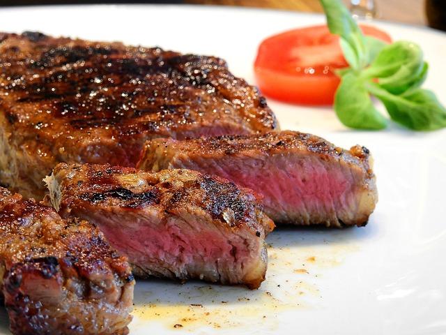 ein weißer Teller auf dem ein medium Steak in Streifen geschnitten ist