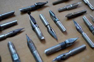 alte Metallfüllfedern die in dreier Gruppen auf einem Karton ausgestellt sind