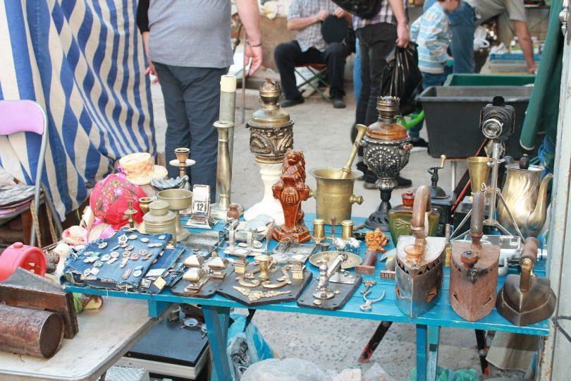 kleiner stand auf einem Flohmarkt, zum verkauf stehen kleine Antiquitäten wie Kerzenhalter und Bügeleisen