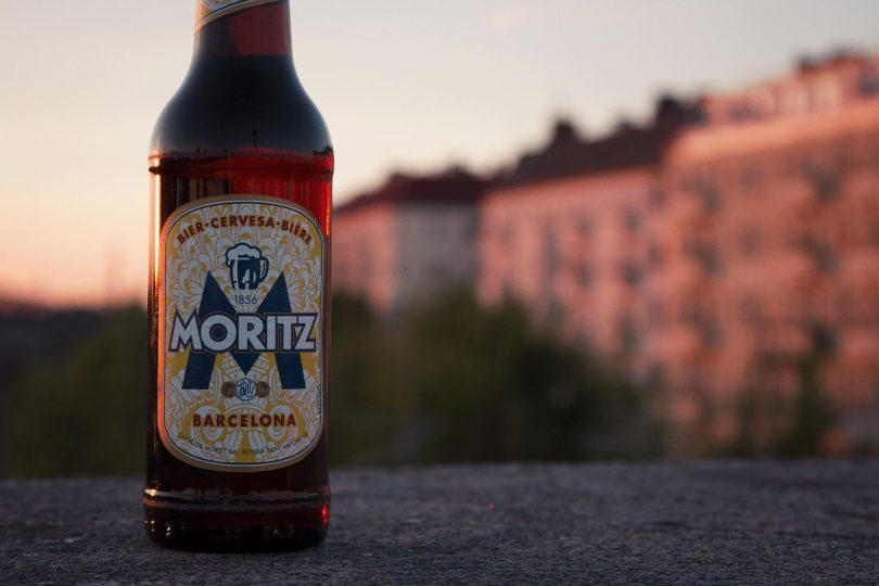 eine Flasche Moritz Bier die auf einer Mauer steht im Hintergrund Wohnhäuser im Licht des Sonnenuntergangs