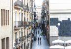 eine Nebenstraße in Barcelona mit kleinen Geschäften und einigen katalanischen Flaggen