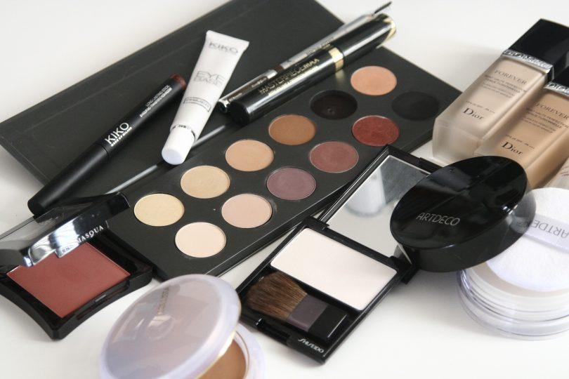 verschieden Kosmetika die auf einem weissen Untergrund quer durcheinander liegen, zum Beispiel eine Palette mit elf Brauntönen für Lidschatten, Pinsel, Bräunungspuder und Flüssig Make-Up
