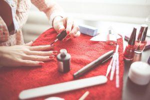eine Frau im kariertem Hemd die auf einem roten Handtuch ihre Fingernägel rot lackiert, drum herum liegen Nagelfeilen, Creme, Nagellackgläschen und andere Sachen