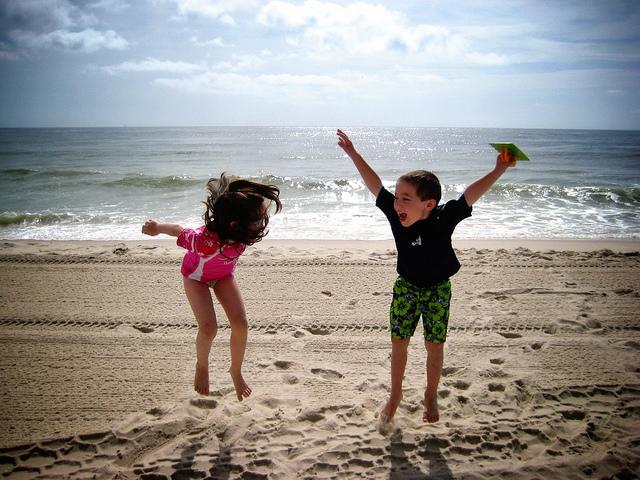 Ein junge mit grüner Badehose und blauem T-Shirt und ein Mädchen mit rosanem Badeanzug die am Strand springen und lachen