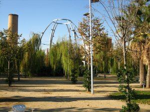 Stadtpark mit Metallgerüst in der Mitte und einem Kamin im Hintergrund