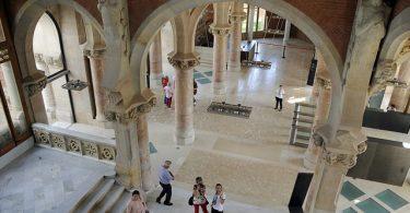 eine der Innenhallen des Krankenhauses, mit gewölbten Decken, Boden und Säulen aus weissem Mamor und vereinzelten Besuchern