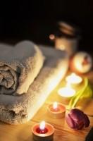 ein Holztischnachts auf einer Terrasse mit angezündeten farbigen Teelichtern und eingerollte Handtücher