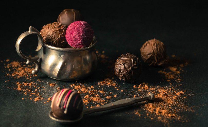 im Vordergrund ein Metalllöffel mit einer runden Schokoladenpraline rechts dahinter zwei weitere Pralinen, eine mit dunkler und eine mit Milchschokolade und links dahinter ein Metallbecher mit drei Pralinen eine davon ist rosa